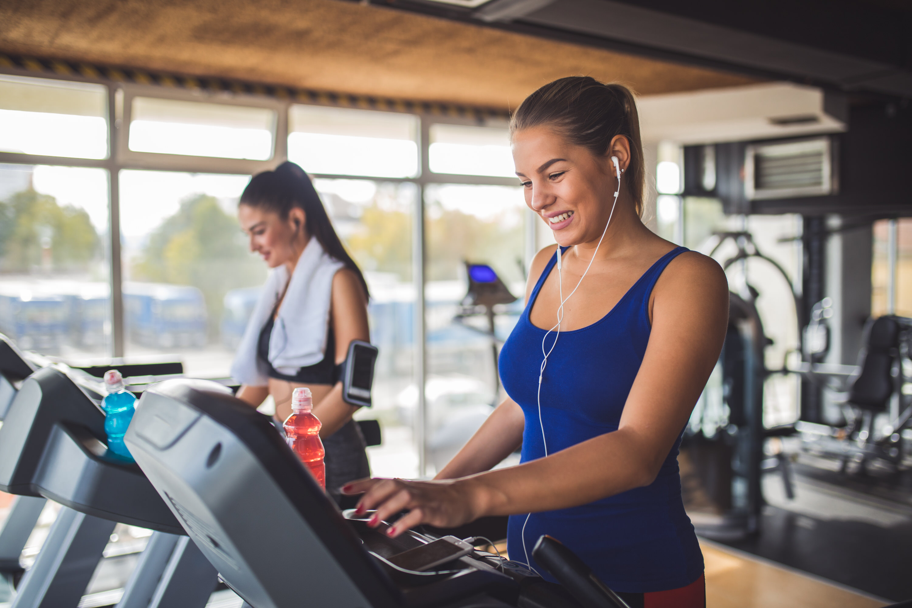 Young woman adjusting speed on a treadmill at gym.