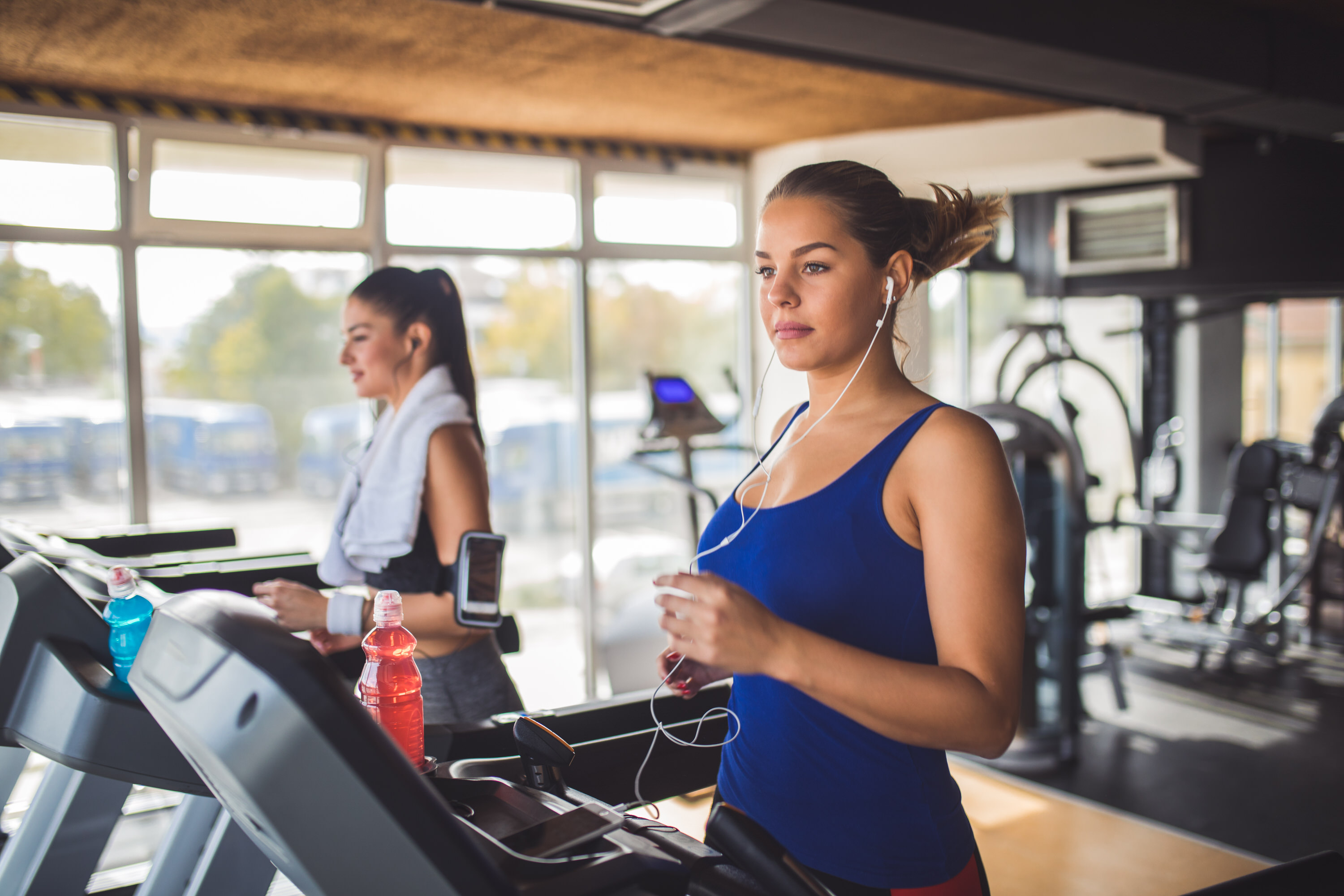 Image of young woman running on treadmill at the gym.