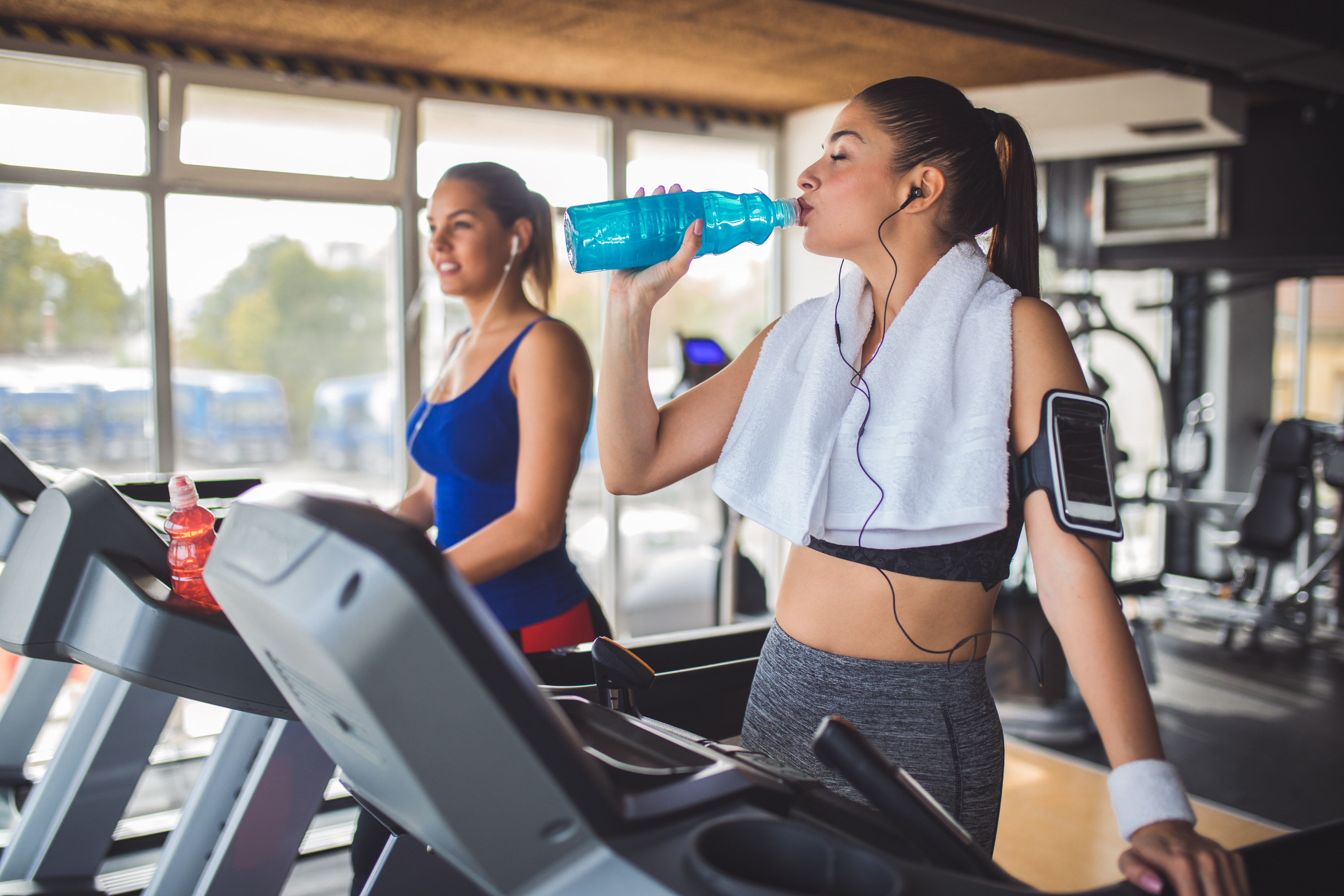 Young women drinking refreshment drink while exercising on treadmill