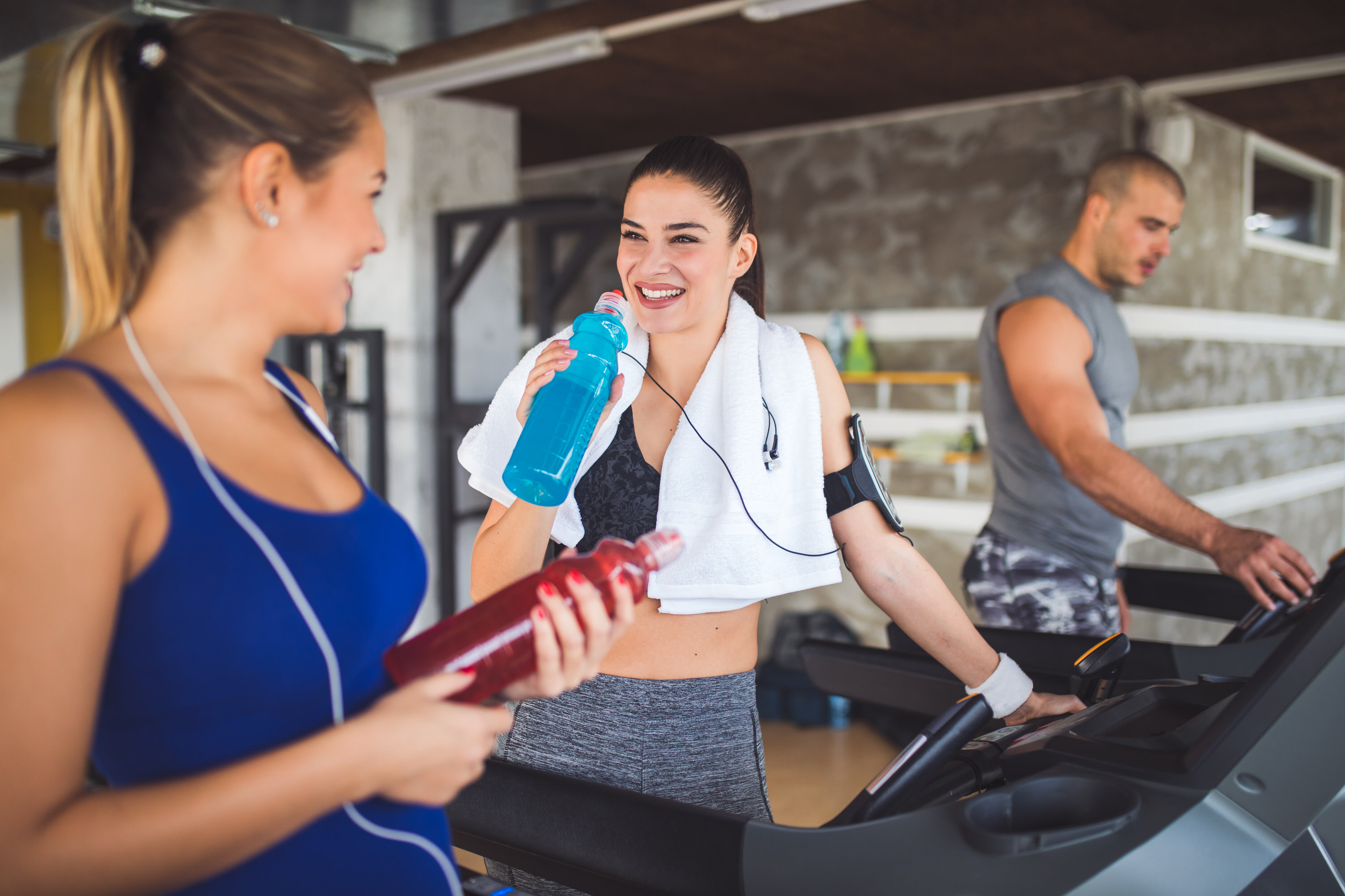 Young women drinking refreshment drink while exercising on treadmill at gym.