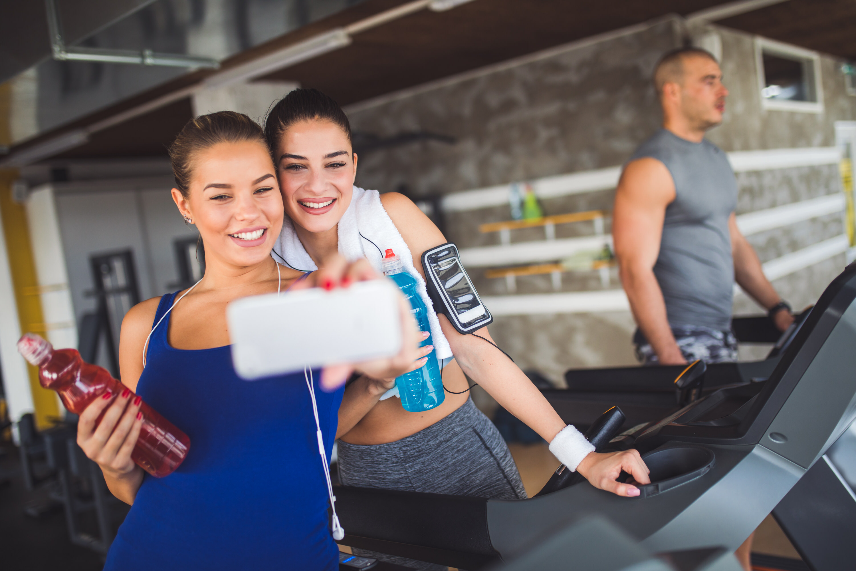 Two young women taking Selfie while working out at the gym.