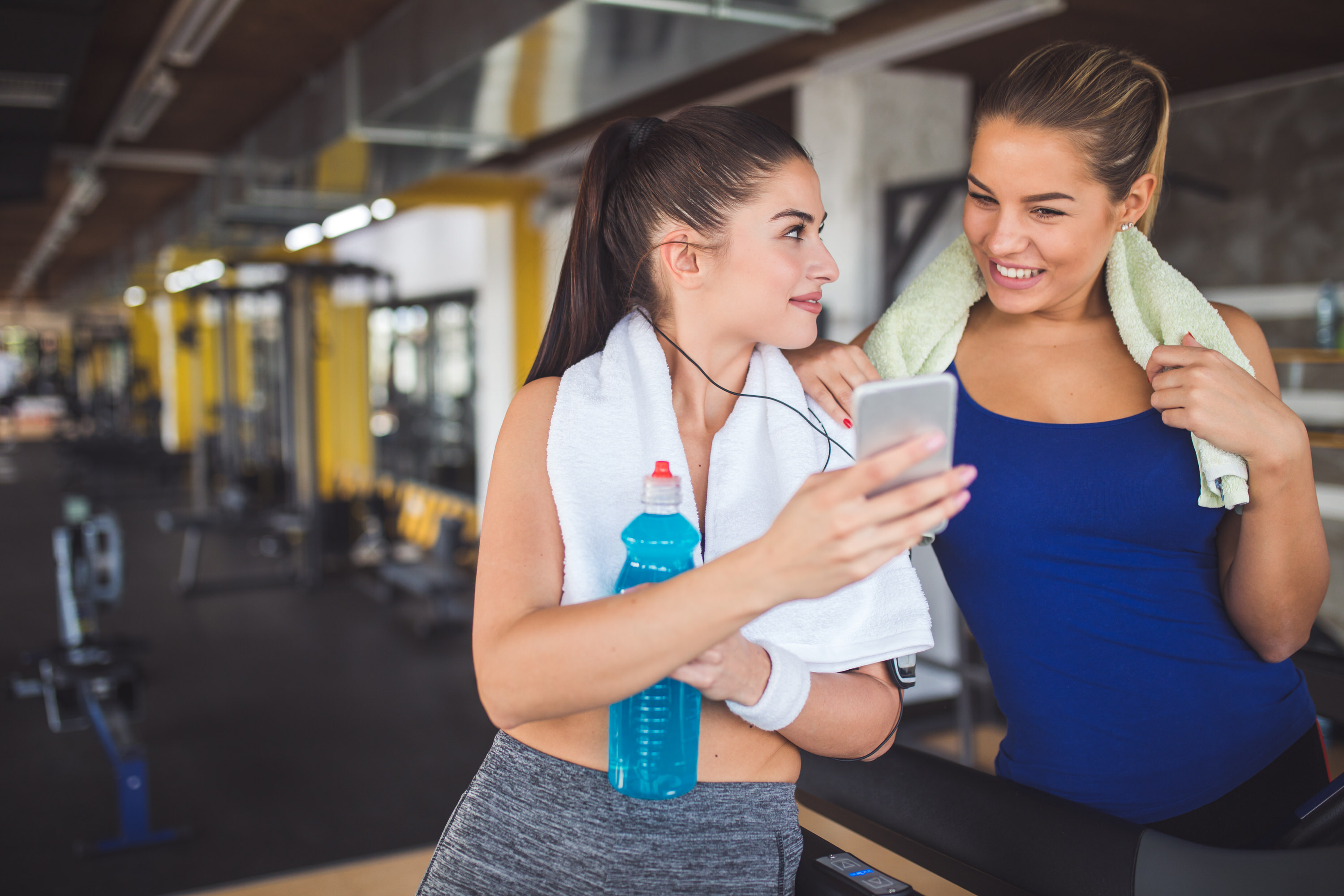 Young women using mobile phone while exercising at gym.