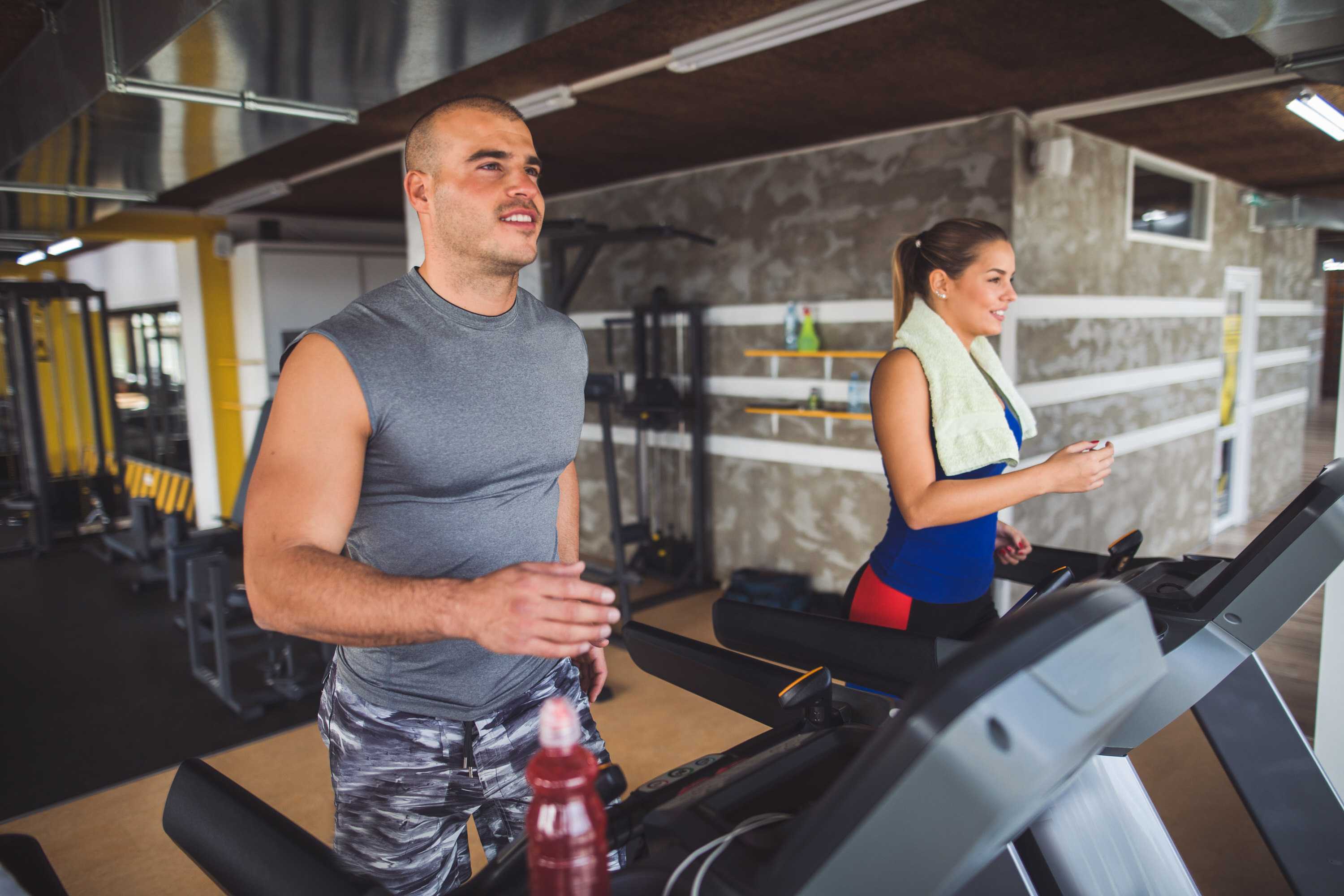 Image of two young sporty people working out on treadmills at the gym.