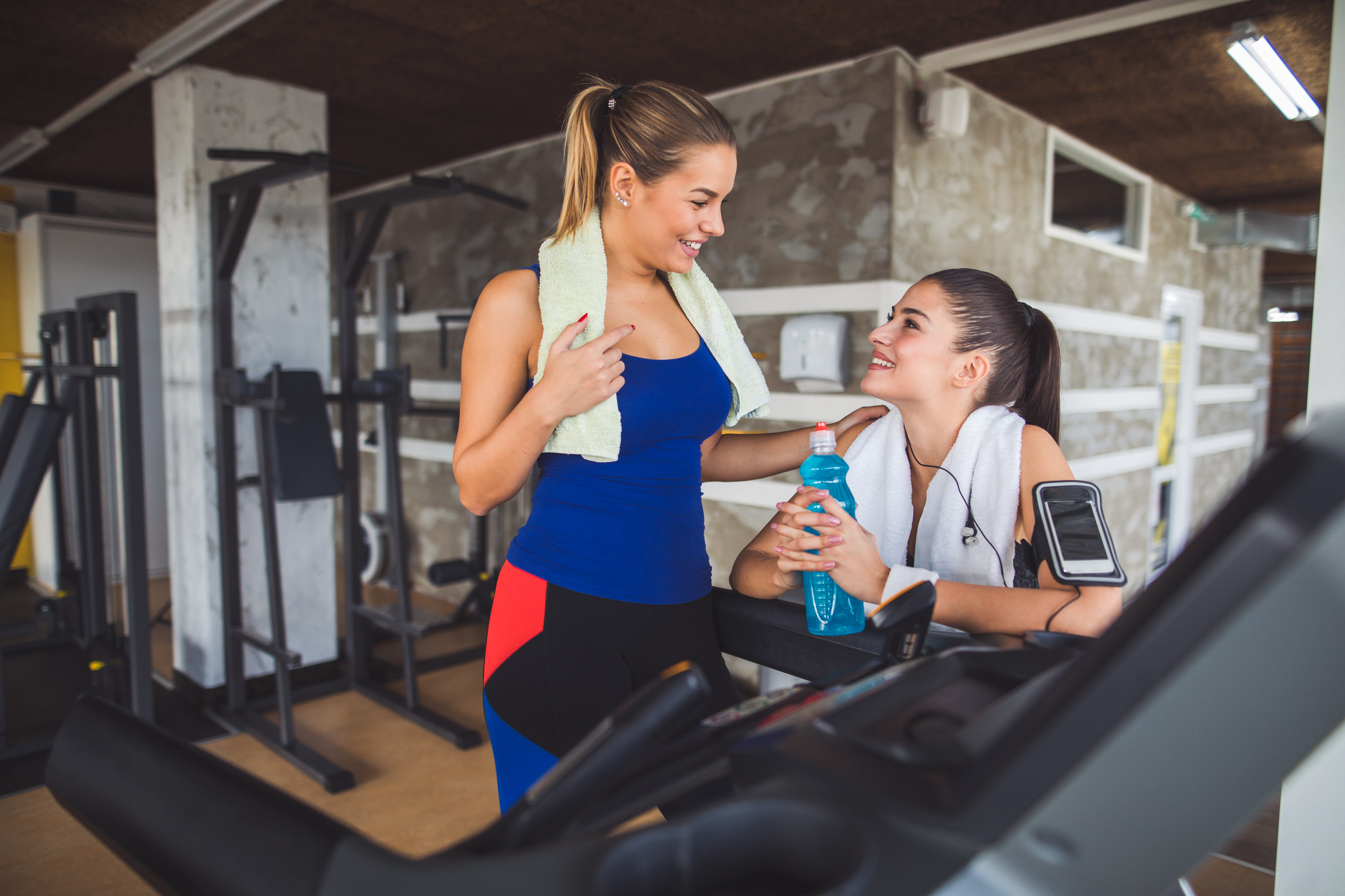 Two young women chatting at the gym while resting from workout