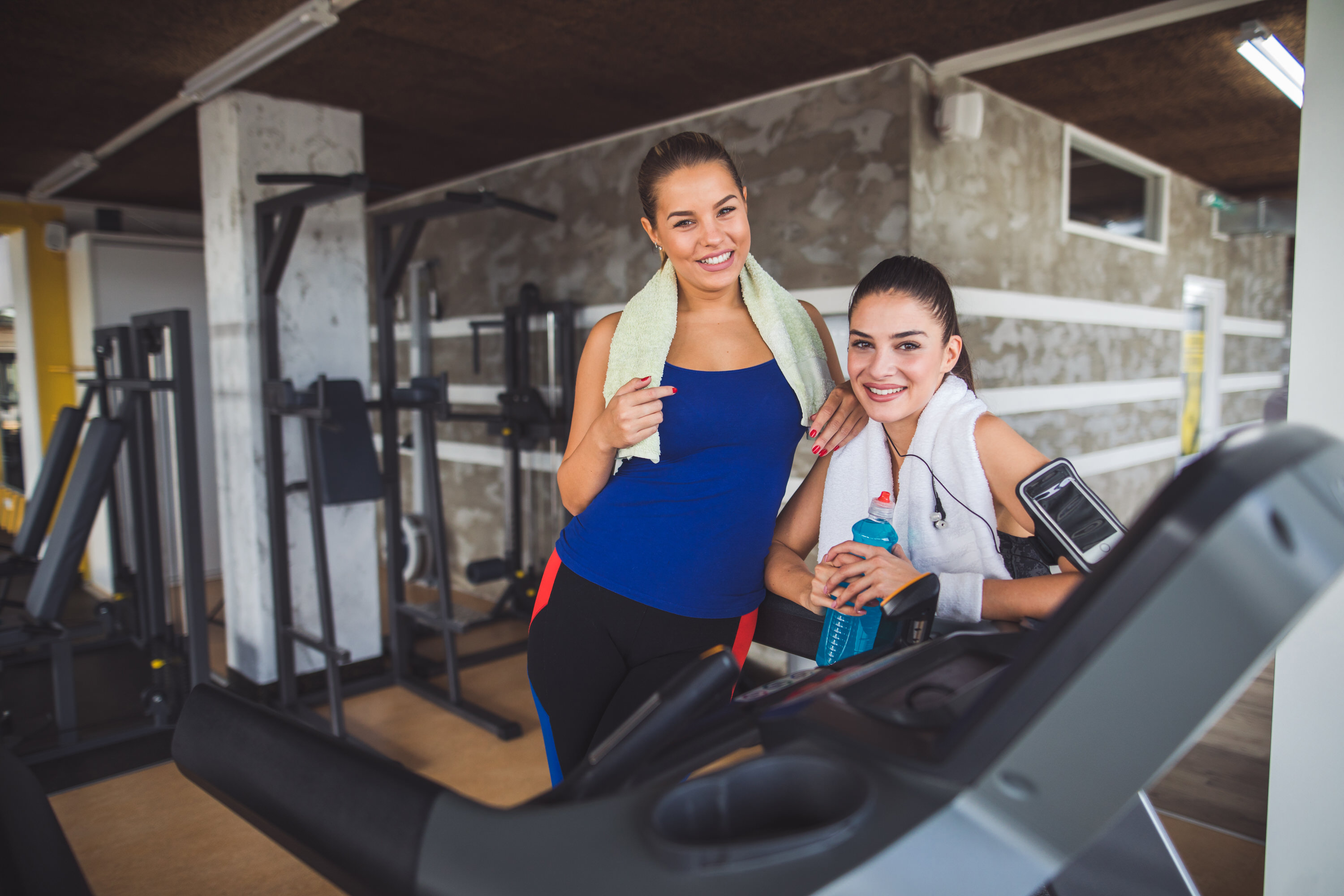 Portrait of two young sporty women at fitness club. Looking at camera.