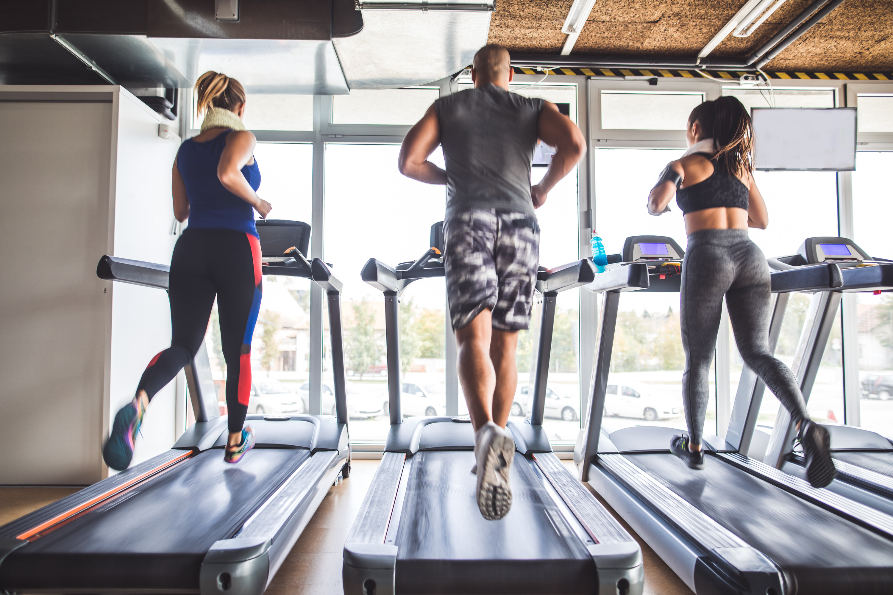 Handsome man and two young beautiful women doing cardio on a treadmill in a gym. Rear view of people working out.