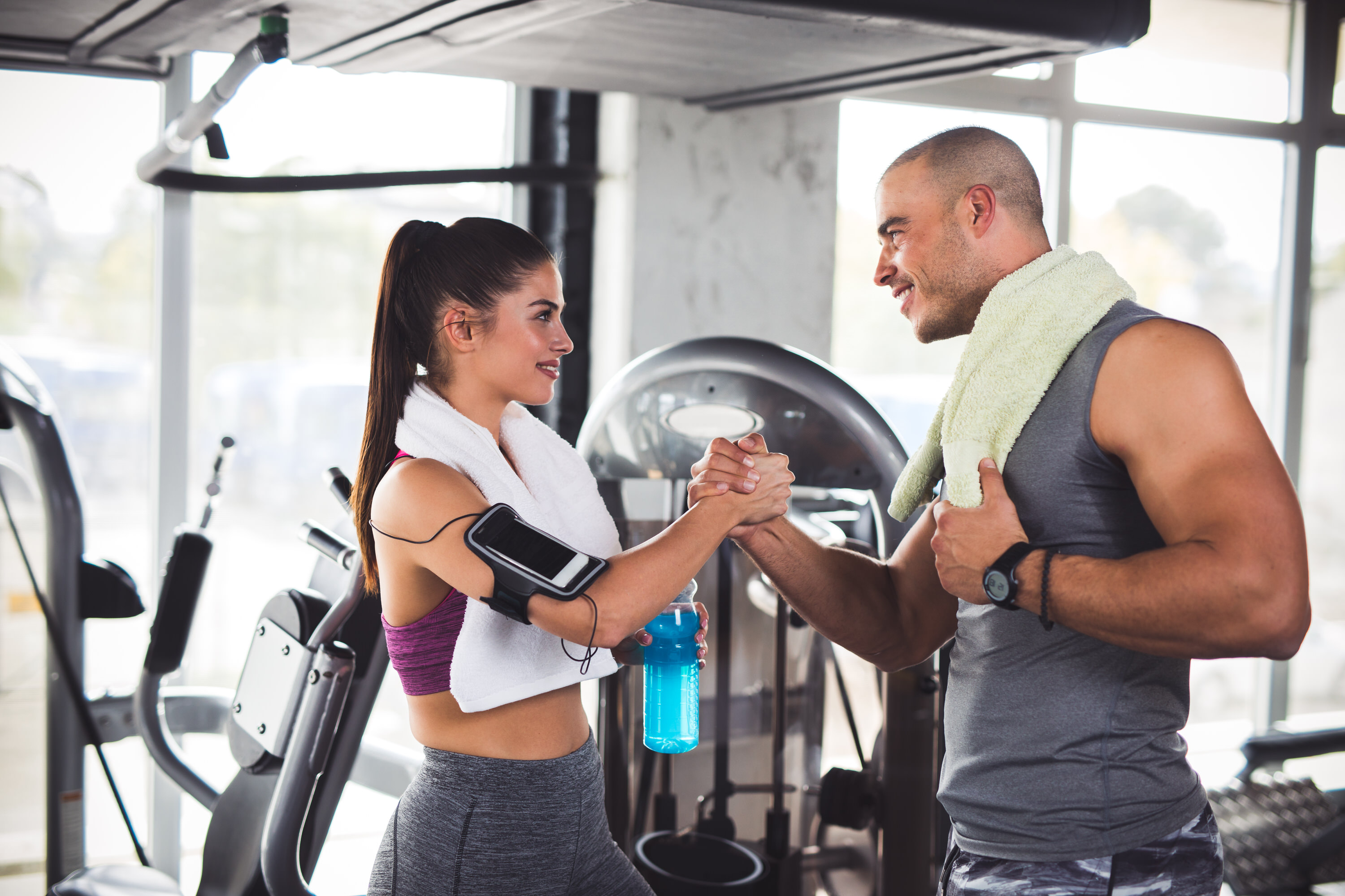 Young sporty woman and her fitness trainer clapping hands after hard workout at the gym..