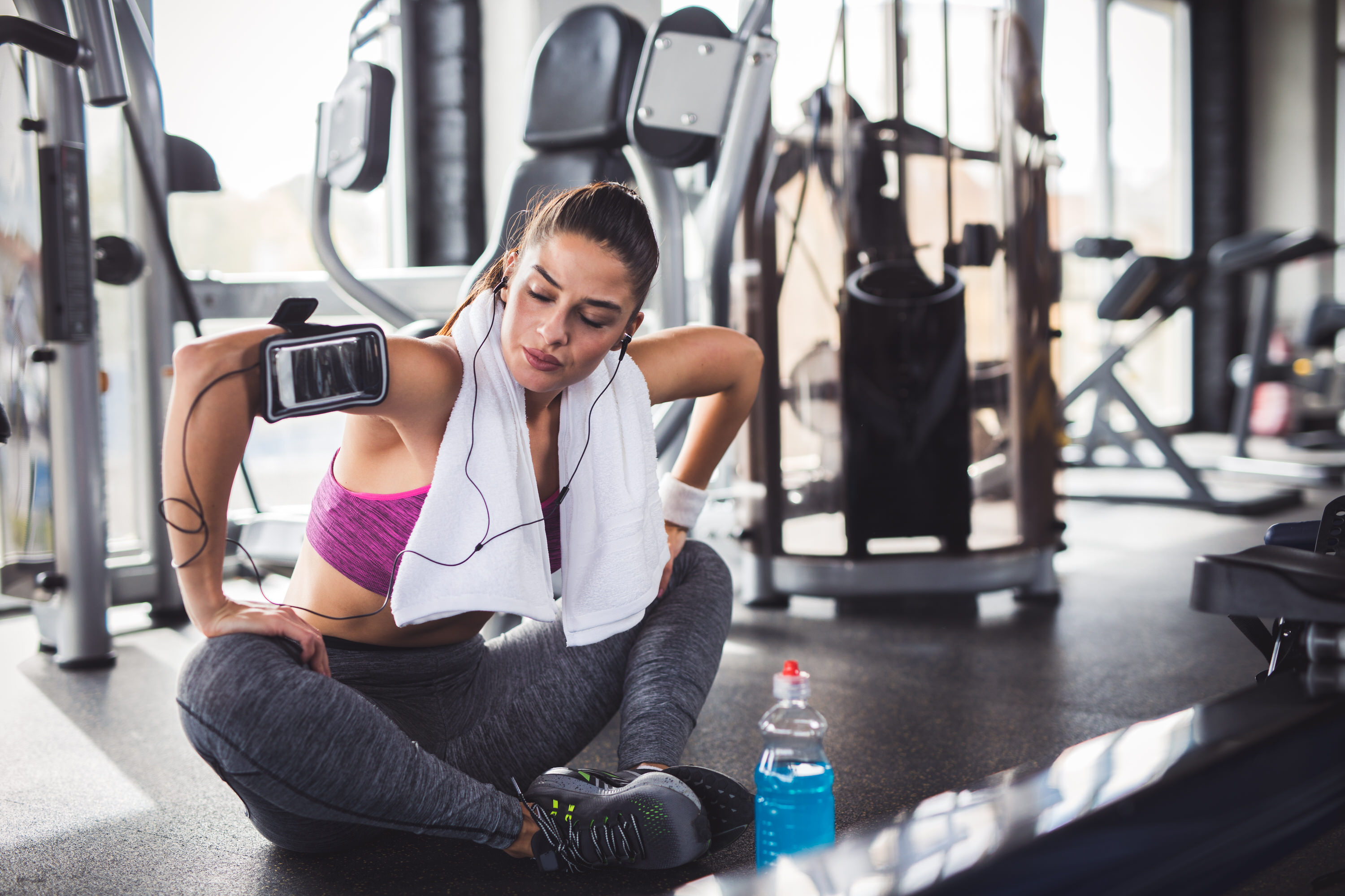 Image of a young sporty woman warming up before her workout at the gym.