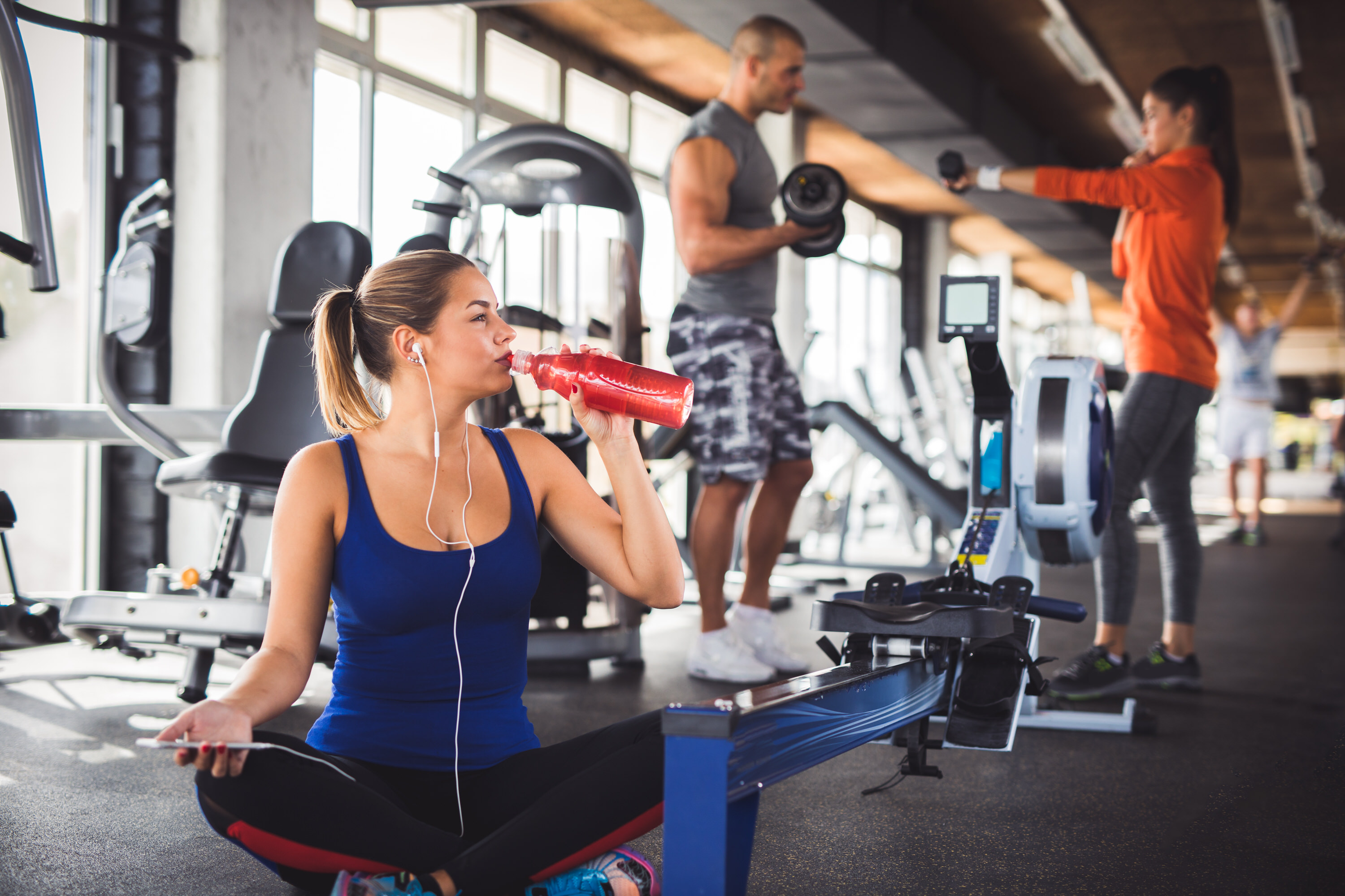 Young woman drinking refreshment drink after workout at gym. There are two people exercising in the background.