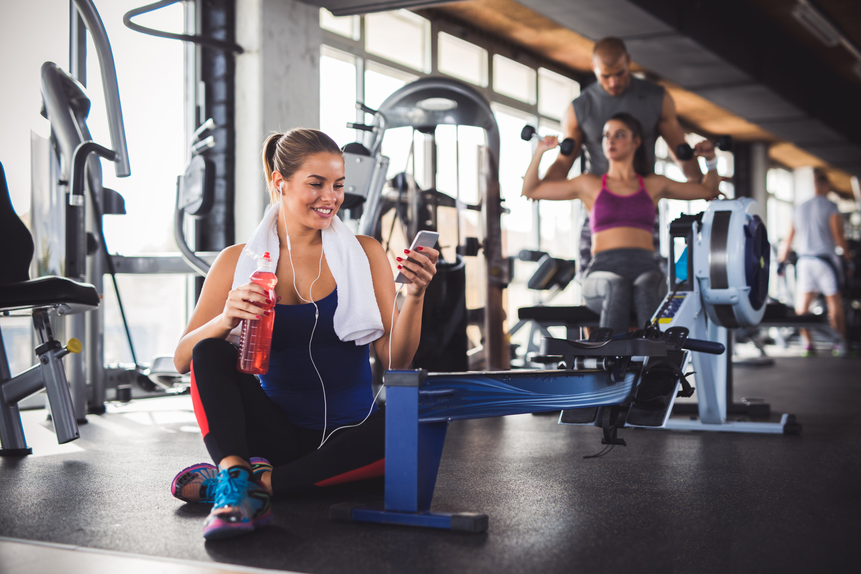 Young sporty woman using mobile phone at the gym while resting from workout. There are two people exercising in the background.